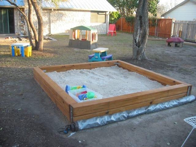 A child raking a sandbox next to his nanny